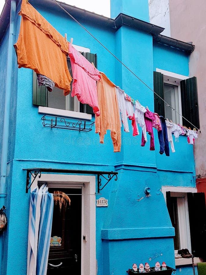 Ropa brillante contra hogares brillantemente coloreados en la isla del burano Venecia Italia imagenes de archivo