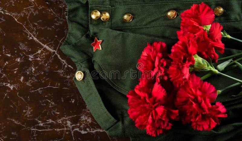 Ropa, casquillo y rosas militares, contra la perspectiva del mármol fotografía de archivo libre de regalías