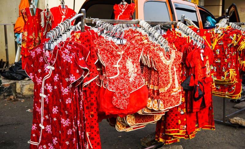 Ropa china de los niños vender en la tienda con color rojo en lado de la calle fotos de archivo libres de regalías