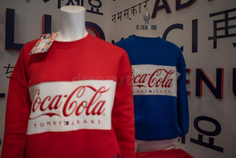 Ropa colorida de la Coca-Cola de Tommy Hilfiger en el mercado superior en el área internacional 1 de la impulsión fotos de archivo libres de regalías