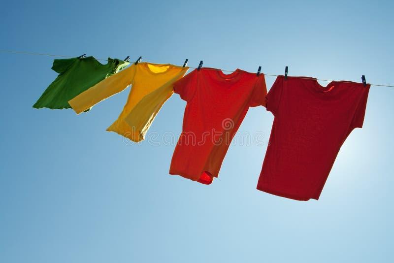 Ropa colorida que cuelga para secarse en el cielo azul imagen de archivo