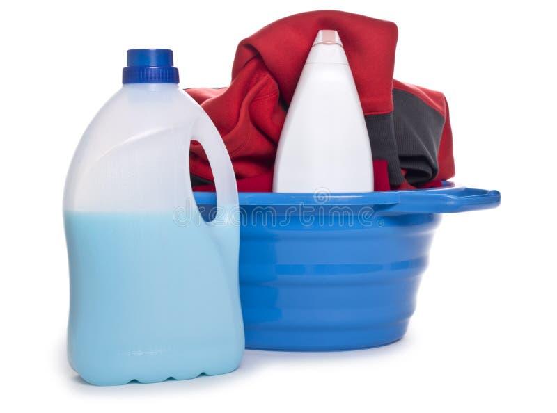 Ropa con el detergente y el detergente en cesta plástica imagen de archivo libre de regalías