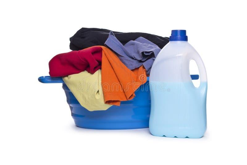 Ropa con el detergente y el detergente en cesta plástica fotos de archivo libres de regalías