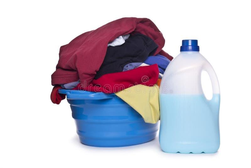Ropa con el detergente y el detergente en cesta plástica fotografía de archivo
