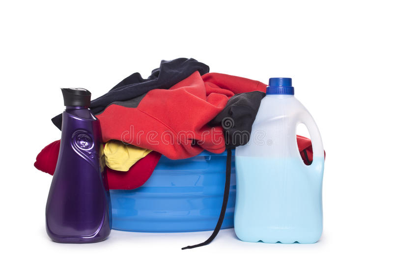 Ropa con el detergente y el detergente en cesta plástica imagen de archivo