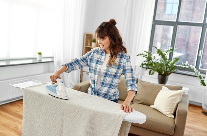 Ropa de cama asiática de la mujer que plancha o del ama de casa en casa fotografía de archivo libre de regalías