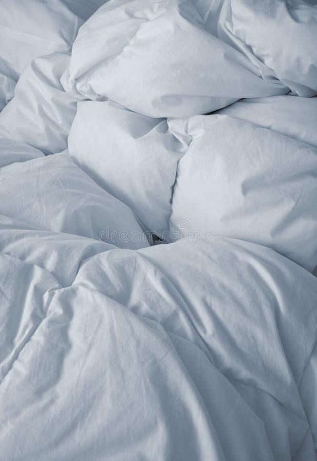 Ropa de cama blanca en vertical imagen de archivo libre de regalías