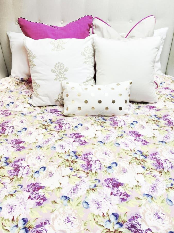 Ropa de cama blanca y púrpura con diseño floral foto de archivo libre de regalías