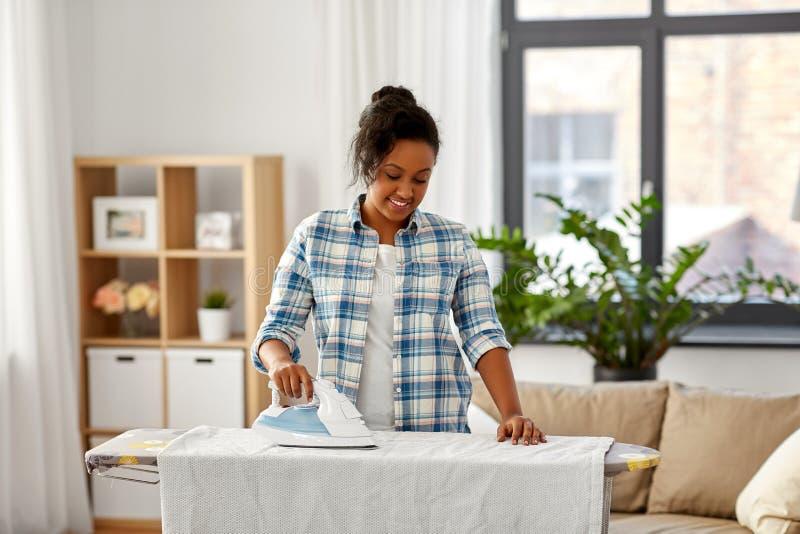 Ropa de cama de la mujer que plancha afroamericana en casa fotografía de archivo libre de regalías