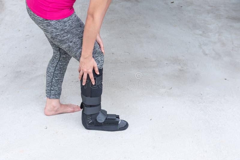 ropa de deportes que lleva herida de la mujer con el apoyo de tobillo negro en la pierna s foto de archivo