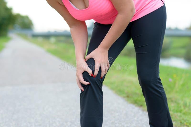 Ropa de deportes que lleva de la mujer que sostiene su rodilla dolorosa imagenes de archivo