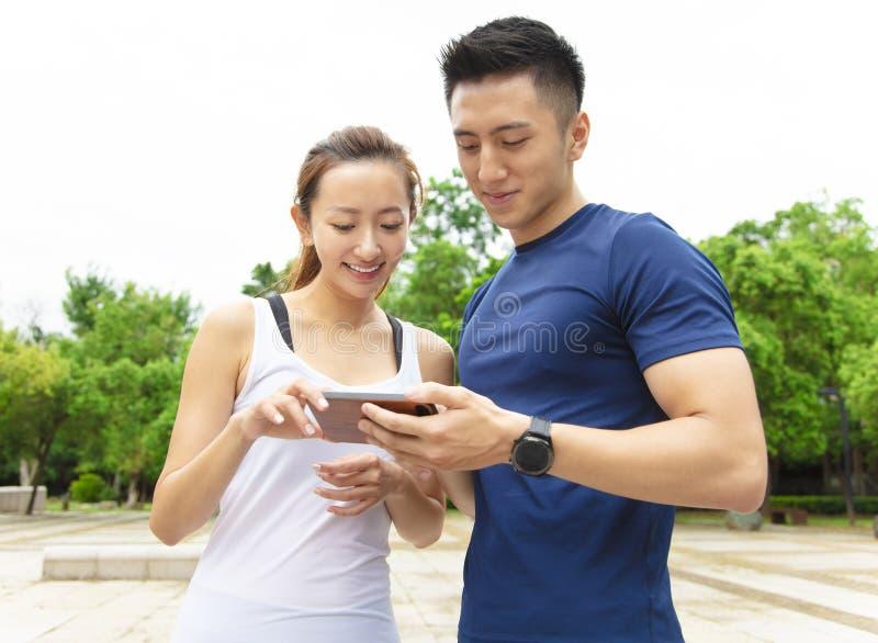 ropa de deportes que lleva de los pares de la aptitud y mirada de smartphone imágenes de archivo libres de regalías
