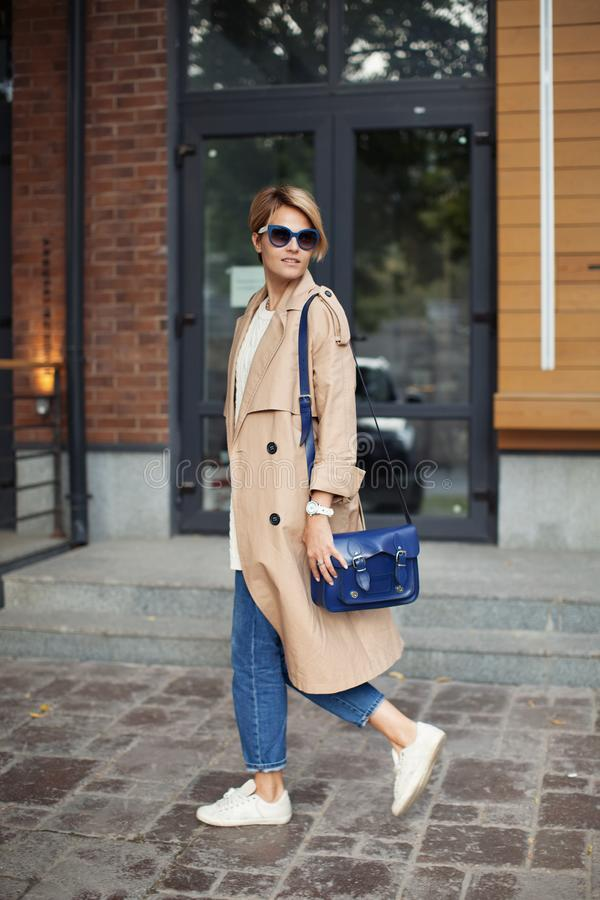 Ropa de la alta moda Mujer hermosa que lleva la primavera de moda o la trenca beige de la ropa de la caída, bolso azul, vaqueros, imagen de archivo