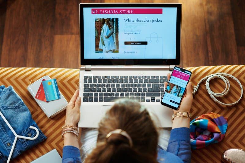 Ropa de la compra de la mujer mientras que tienda en línea en el ordenador portátil y el smartphone imagen de archivo