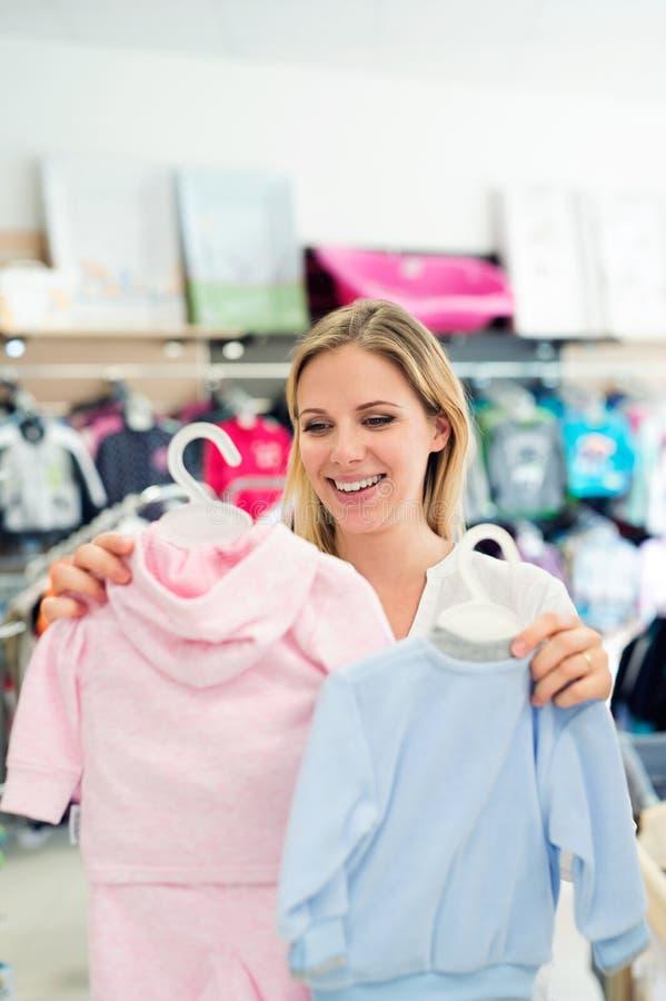 Ropa de las compras de la mujer embarazada para su bebé imágenes de archivo libres de regalías