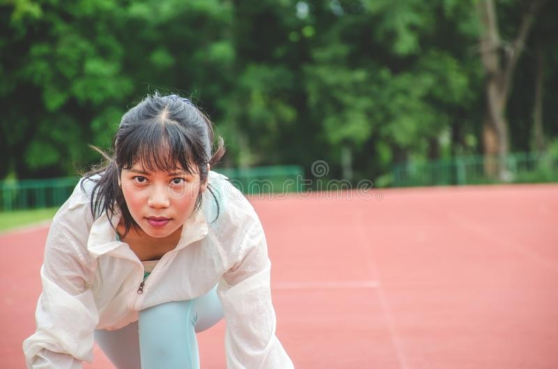 Ropa de los deportes de la mujer que lleva joven y listo para comenzar a correr en la pista en el estadio, mujeres del deporte fotos de archivo libres de regalías