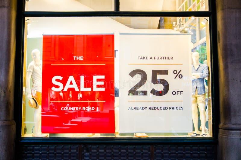 Ropa de moda de la carretera nacional y tienda al por menor de los accesorios con el 25% de muestra roja de la venta en la ventan fotografía de archivo