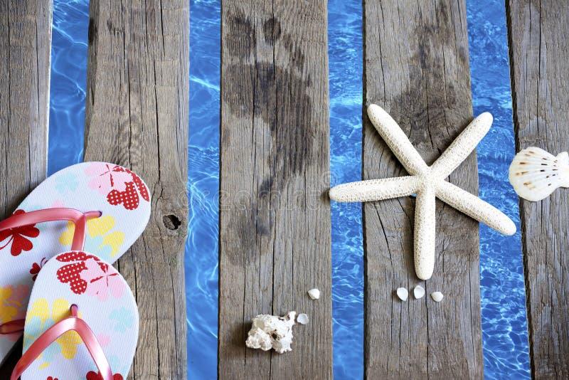 Ropa de playa en el embarcadero en el fondo de las vacaciones del día de fiesta del mar imagen de archivo libre de regalías