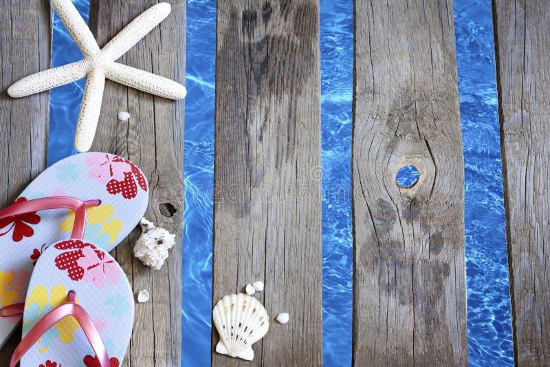 Ropa de playa en el embarcadero en el fondo de las vacaciones del día de fiesta del mar foto de archivo libre de regalías