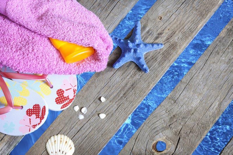 Ropa de playa en el embarcadero en el fondo de las vacaciones del día de fiesta del mar fotografía de archivo