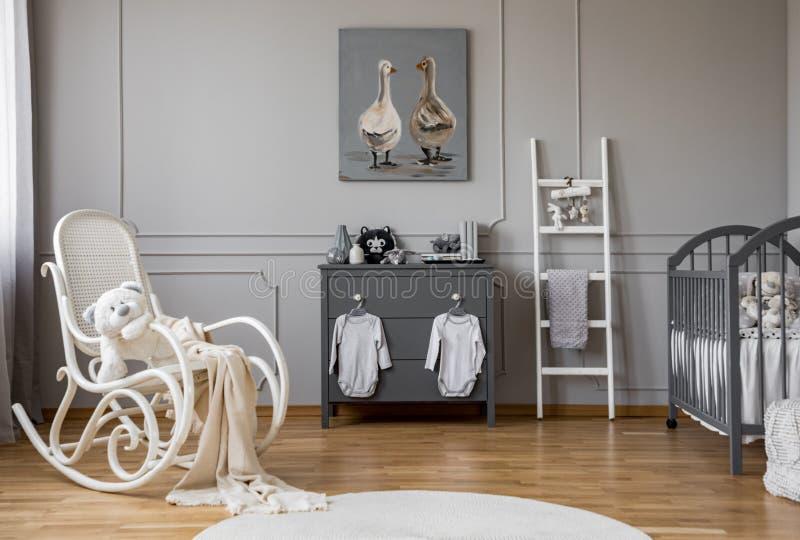 Ropa del bebé que cuelga en botones en cómoda de madera gris en cuarto de niños, espacio de la copia y cartel preciosos en la par foto de archivo libre de regalías