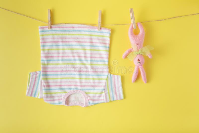 Ropa del bebé y conejo de pascua en una cuerda para tender la ropa imagen de archivo libre de regalías