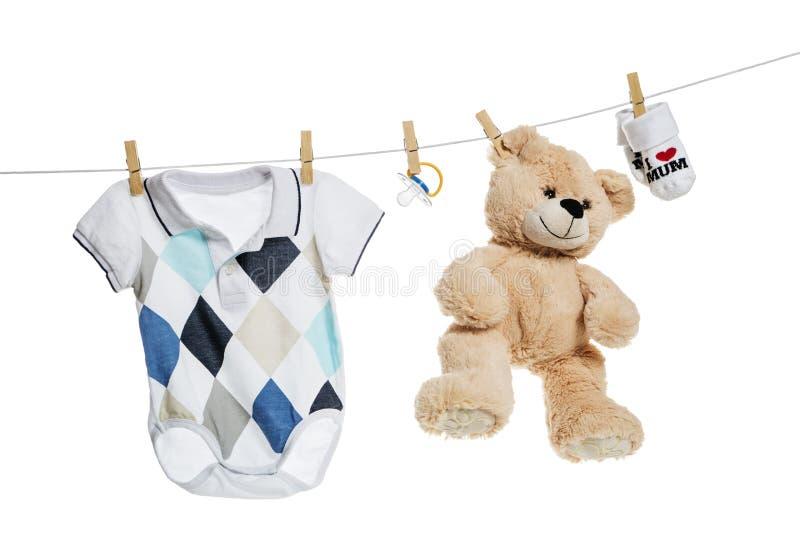 Ropa del bebé y ejecución del oso de peluche en la cuerda para tender la ropa fotos de archivo libres de regalías