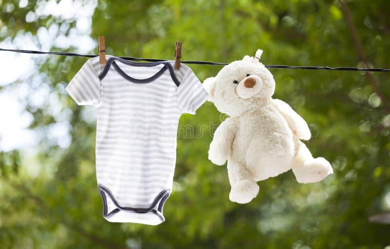 Ropa del bebé y ejecución del oso de peluche en la cuerda para tender la ropa fotos de archivo