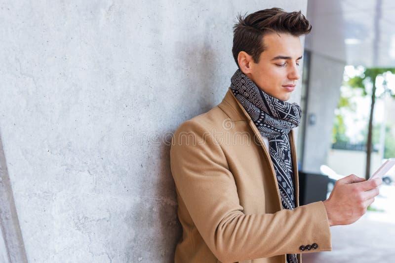 Ropa del invierno del hombre que lleva joven en la calle usando el teléfono Individuo joven con el peinado moderno con la capa, l imágenes de archivo libres de regalías