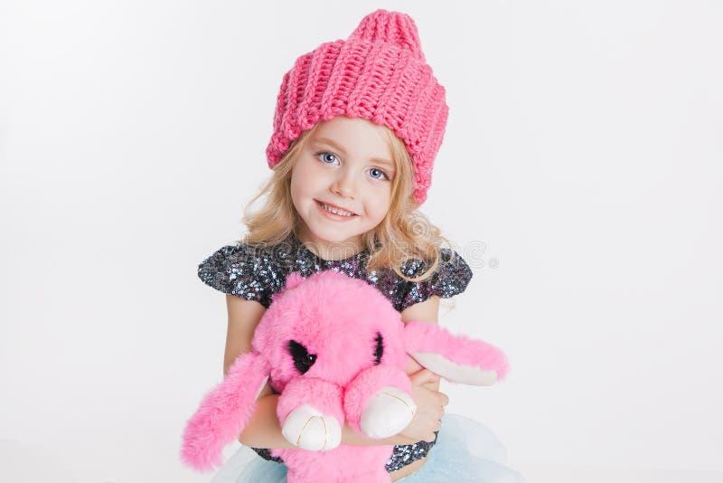 Ropa del invierno Retrato de la pequeña muchacha rizada en sombrero rosado hecho punto del invierno en blanco Juguete rosado del  imagen de archivo libre de regalías
