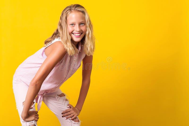 Ropa del verano de la moda de la muchacha que lleva pre-adolescente linda que presenta en fondo amarillo 10 años de la muchacha c fotos de archivo