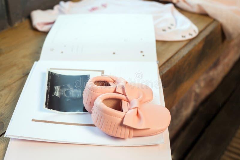 Ropa del vestido del rosa del bebé con el álbum recién nacido del libro, cuerpo y pequeños zapatos y ultrasonido explorando la fo imagen de archivo libre de regalías