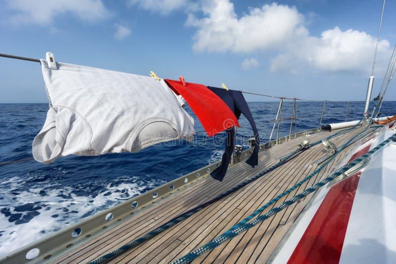 Ropa divertida de la ejecución en el barco de vela imagen de archivo