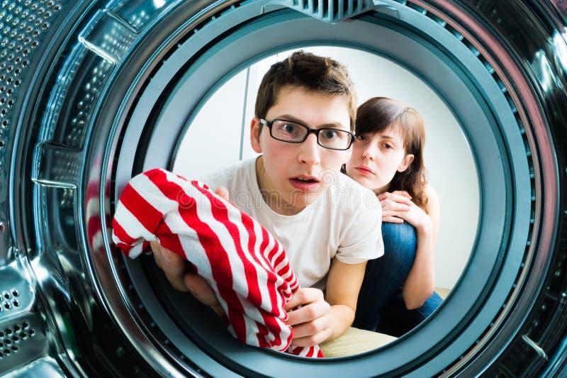 Ropa divertida del cargamento de los pares a la lavadora imagenes de archivo