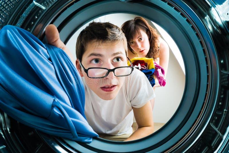 Ropa divertida del cargamento de los pares a la lavadora imágenes de archivo libres de regalías