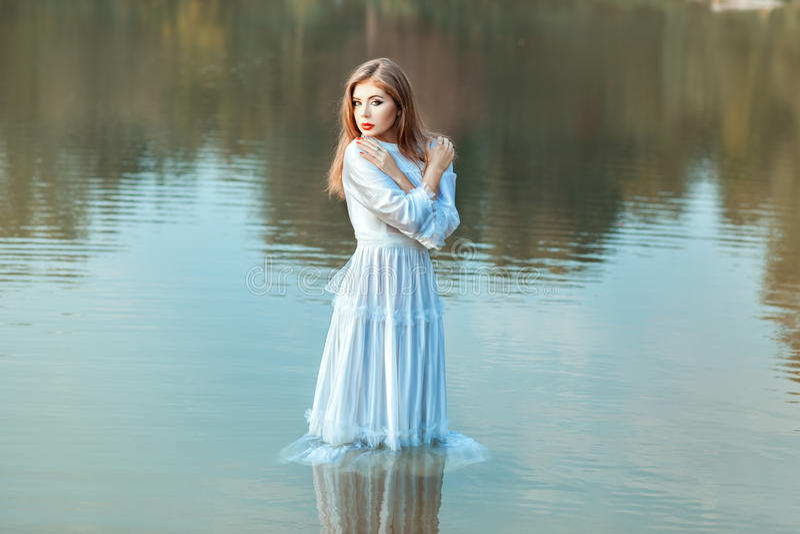 Ropa empapada muchacha en el agua del lago imágenes de archivo libres de regalías