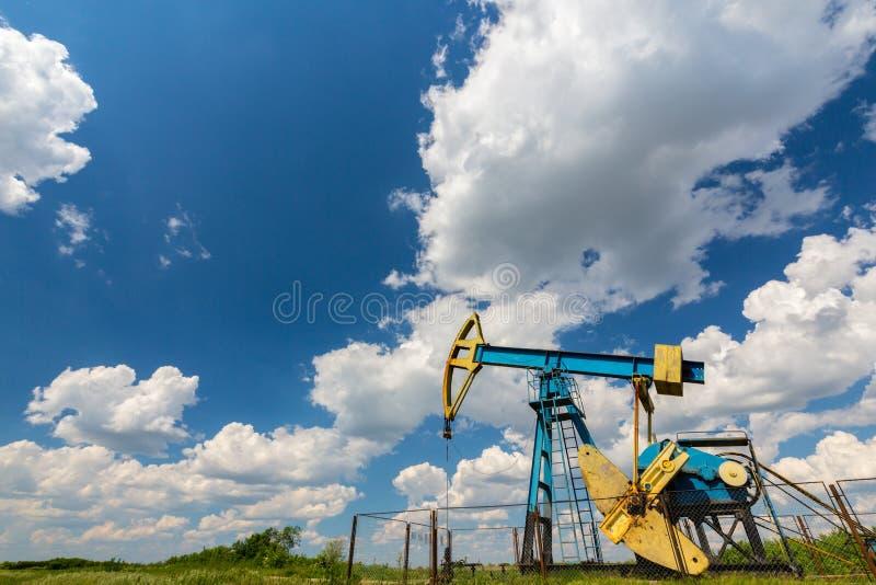 Ropa i gaz well profilujący na niebieskim niebie z cumulus chmurami w Europa, fotografia royalty free