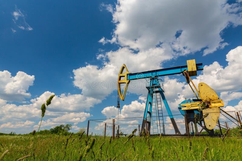 Ropa i gaz well profilujący na niebieskim niebie z cumulus chmurami w Europa, obrazy stock