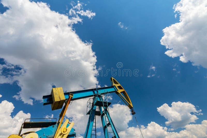 Ropa i gaz well profilujący na niebieskim niebie z cumulus chmurami w Europa, fotografia stock