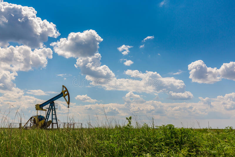 Ropa i gaz well profilujący na niebieskim niebie z cumulus chmurami w Europa, obraz royalty free