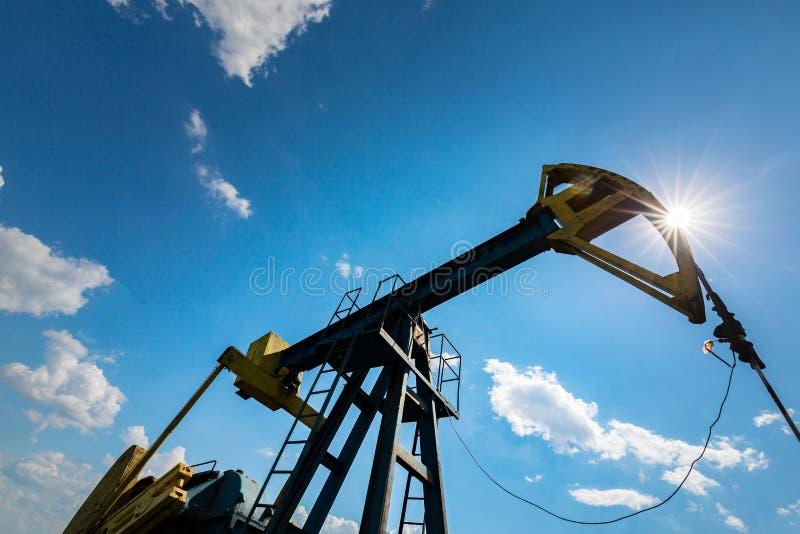 Ropa i gaz well profilujący na niebieskim niebie z cumulus chmurami w Europa, obraz stock