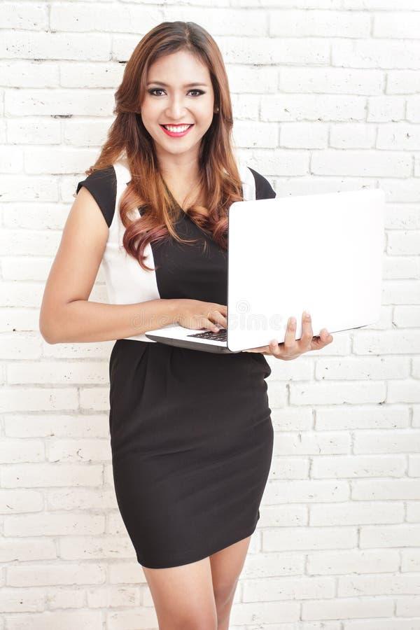 Ropa informal que lleva permanente de la mujer hermosa mientras que sostiene un la imagenes de archivo