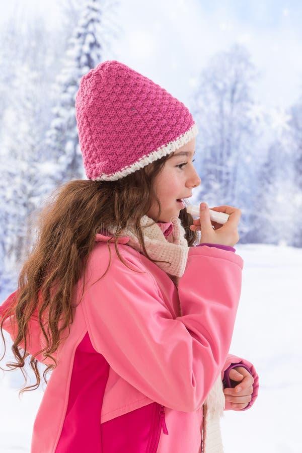 Ropa linda de la muchacha que aplica protector labial imagenes de archivo