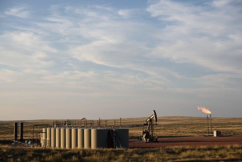 Ropa naftowa dobrze jest usytuowanym, produkcji mienia zbiorniki, pompowa dźwigarka i gazu naturalnego migotać, obraz stock