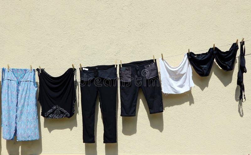 Ropa oscura que cuelga hacia fuera para secar en una cuerda para tender la ropa por el lado una pared imagen de archivo libre de regalías