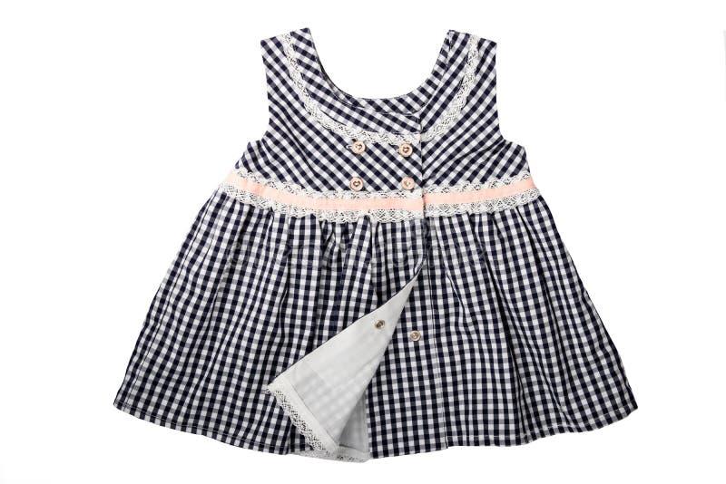 Ropa para los niños Un vestido a cuadros blanco y negro con el perno imágenes de archivo libres de regalías