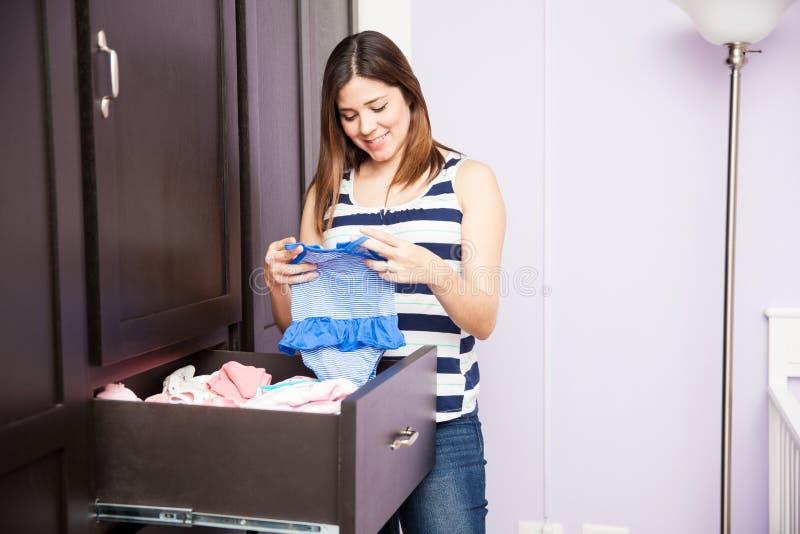 Ropa plegable del bebé en un armario fotos de archivo