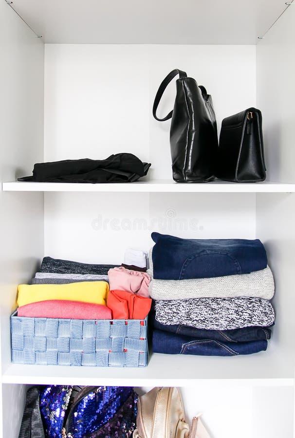 Ropa que clasifica en el guardarropa casero Diversos artículos de la ropa y accesorios del bolso en el estante blanco imágenes de archivo libres de regalías