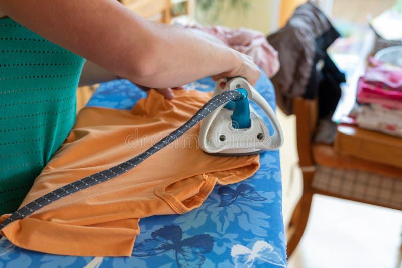 Ropa que plancha de la mujer en casa una camiseta anaranjada fotos de archivo libres de regalías