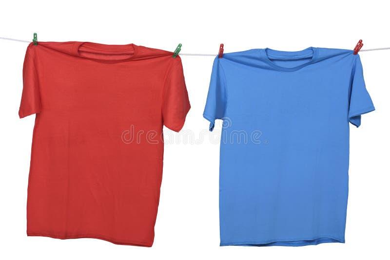 Ropa roja y azul que cuelga en la cuerda para tender la ropa fotos de archivo libres de regalías